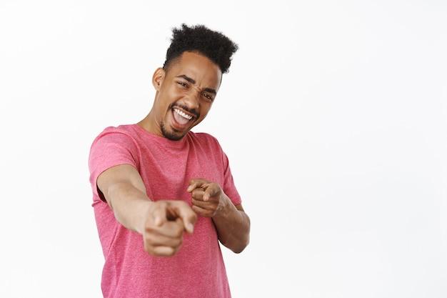 おめでとうございます。笑顔のアフリカ系アメリカ人男性が指を指して、笑ってニヤリと笑い、招待する人を選び、勝者におめでとう、賞賛、白の上に立つ