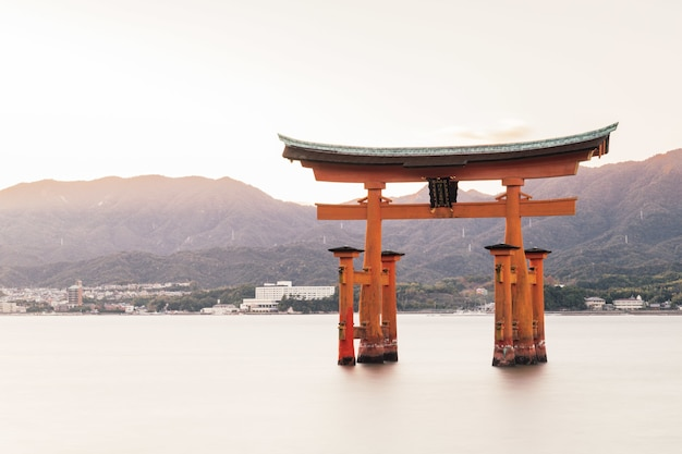 Itsukushima shrine in a lake surrounded by hills covered in greenery in japan