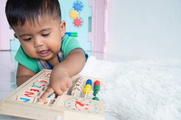 Ittle baby boy lying and play wooden toy
