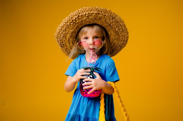Ittle blonde girl in a straw hat and sunglasses is smiling on a yellow background