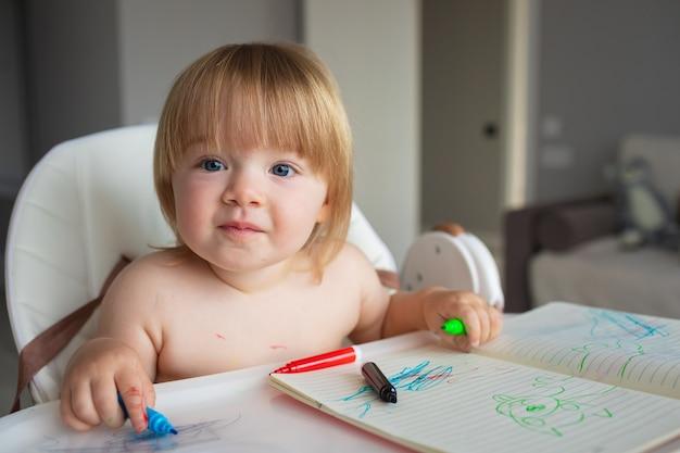 Ittle 백인 여자 아이는 펠트 펜으로 그리고 페인트에 모두 더러워집니다