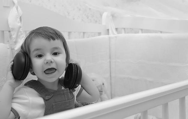 어린 아이는 헤드폰 음악 흑백 사진을 듣습니다.