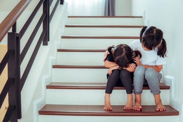 집에서 여동생을 위로하는 어린 소녀