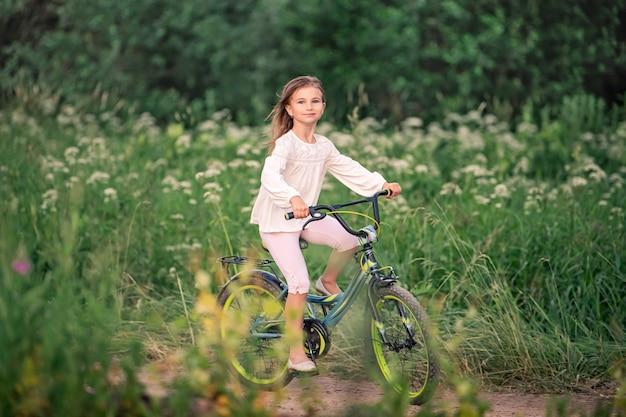 Маленькая девочка едет на велосипеде по сельской дороге на природе в парке среди высоких полевых цветов. быстро мчится, волосы развеваются на ветру.