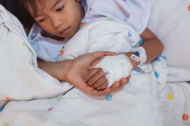 Ivソリューション包帯を持っている病気の娘の手を握っている母の手