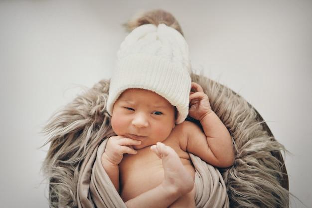 生まれたばかりの赤ちゃんが頭に暖かい帽子をかぶった毛布に包まれました。小児期、健康、ivf。
