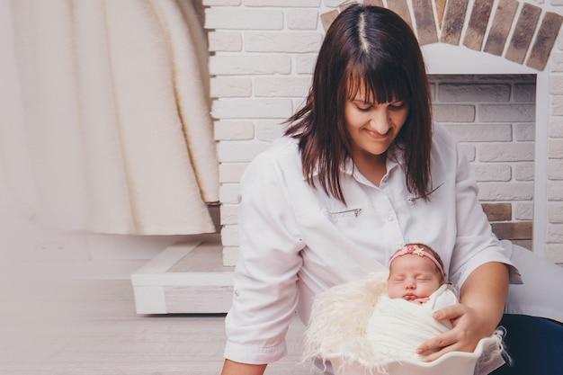 母親は赤ちゃんを抱擁します。毛布にくるまれた生まれたばかりの赤ちゃんは、暖炉を背景にバスケットで眠ります。幼年期、ヘルスケア、ivf、家族の家の概念