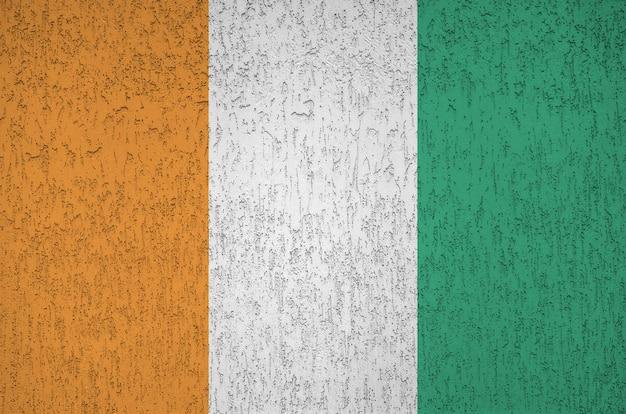 Ivory coast flag depicted in bright paint colors on old relief plastering wall. textured banner on rough background