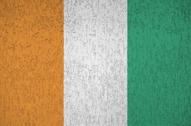 古いレリーフ漆喰壁に明るいペンキ色で描かれたコートジボワールの国旗。大まかな背景に織り目加工のバナー