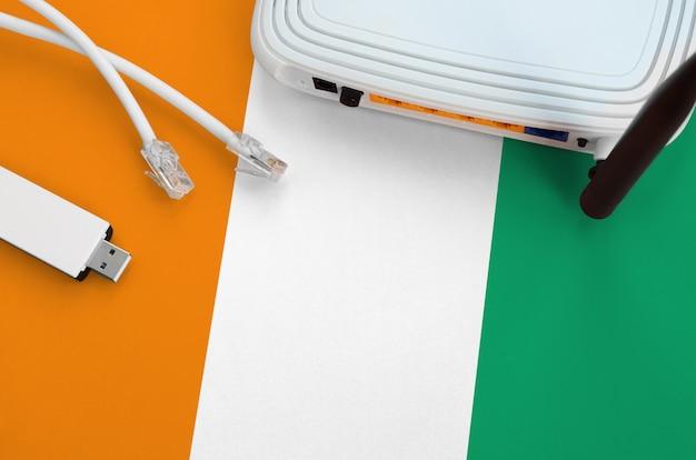 Флаг слоновой кости, изображенный на столе с интернет-кабелем, беспроводным usb-адаптером wi-fi и маршрутизатором. интернет концепции связи фон