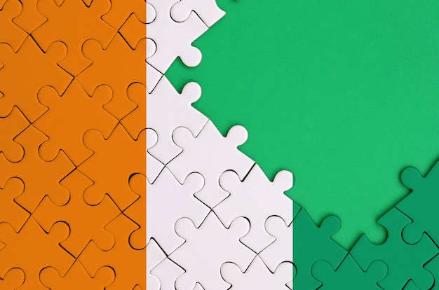 Ivory coast flag  is depicted on a completed jigsaw puzzle with free green copy space on the right side