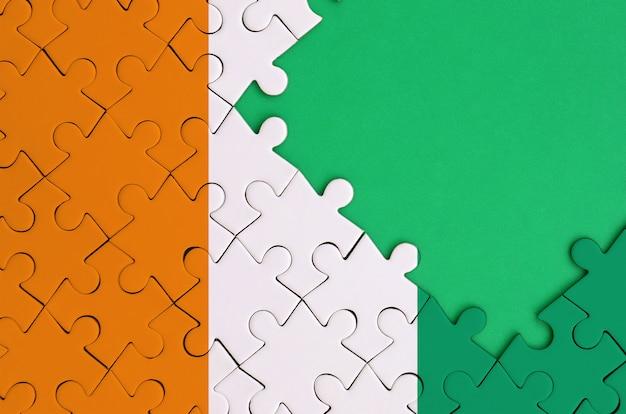 코트 디부 아르 국기는 오른쪽에 무료 녹색 복사 공간이있는 완성 된 직소 퍼즐로 그려져 있습니다.
