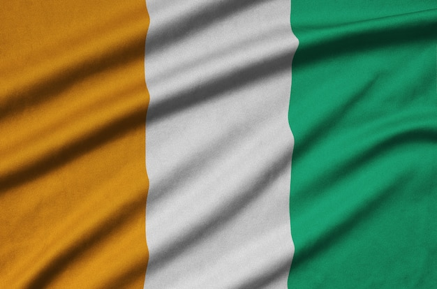 Ivory coast flag  is depicted on a sports cloth fabric with many folds.