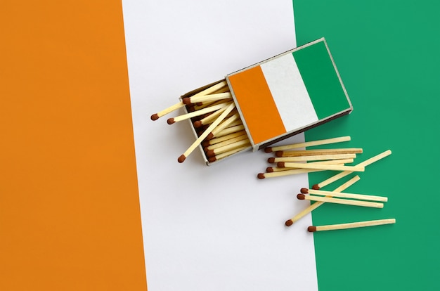 Ivory coast flag  is shown on an open matchbox, from which several matches fall and lies on a large flag