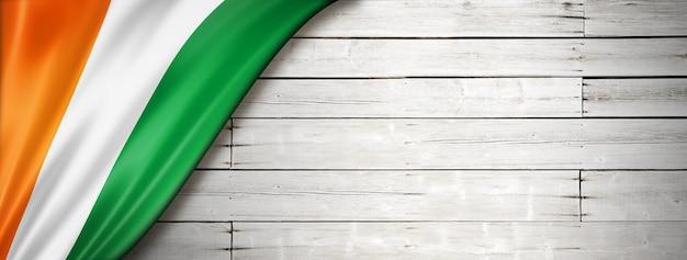 Флаг кот-д'ивуара на старой белой стене. горизонтальный панорамный баннер.