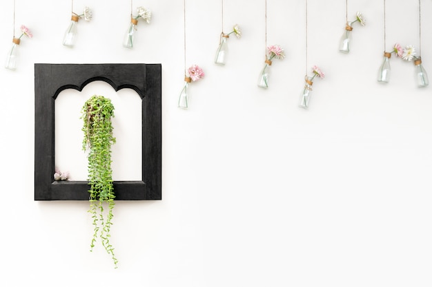 Ivy in black wooden frame on white wall with flowers in hanging bottles.