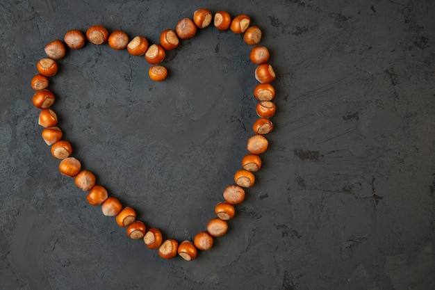 Вид сверху целых лесных орехов, расположенных в форме сердца на темном j