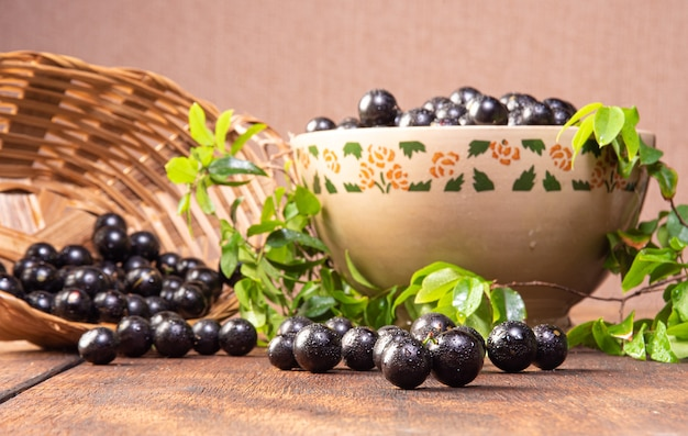 Jabuticaba, jabuticabas freshly harvested in pots and baskets arranged on rustic wood, selective focus.
