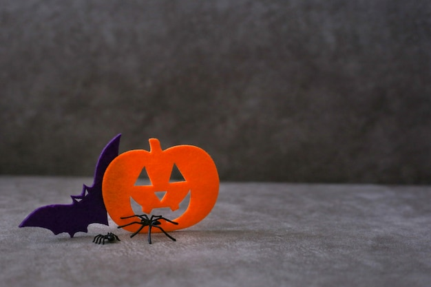 Jack o lantern and bat made of felt next to spiders on brown background