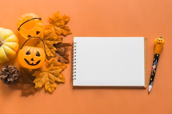 Jack-o-lantern buckets and autumn symbols near notebook and pen