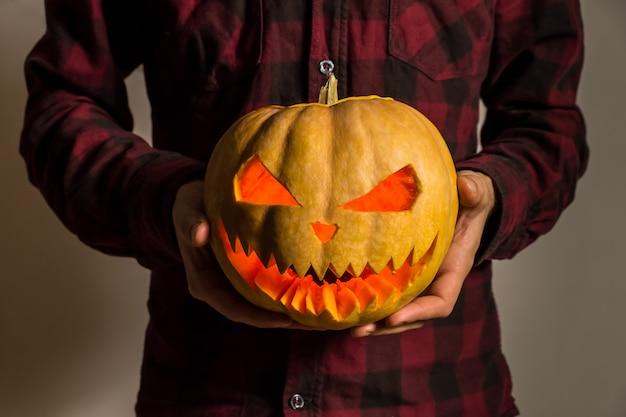 Jack'o'lantern carved pumpkin in hands