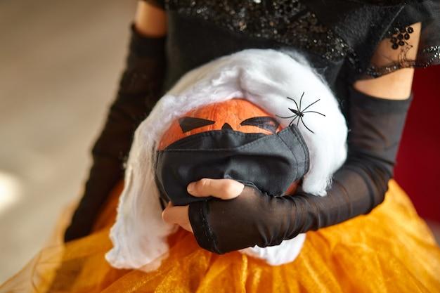 Джек о фонарь, хэллоуин тыква в черной маске медицинской защиты в руках девушки во время празднования хэллоуина дома пандемия коронавируса covid19, копия пространства.