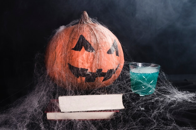 Jack-o'-lantern with spiderweb on books