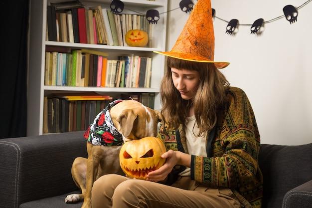 Девушка в шляпе хэллоуина сидит с любопытной собакой, которая сует свой нос в jack'o'lantern