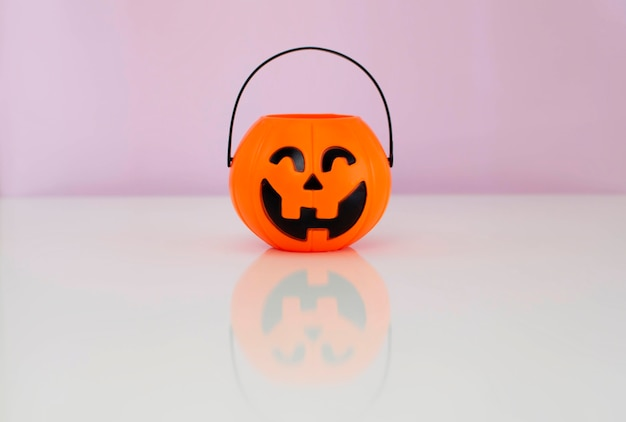 Jack'o pumpkin basket for collecting candy on halloween day on a pink background, a place to copy.
