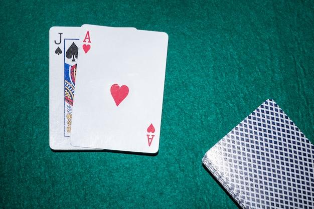 녹색 포커 테이블에 스페이드와 하트 에이스 놀이 카드의 잭