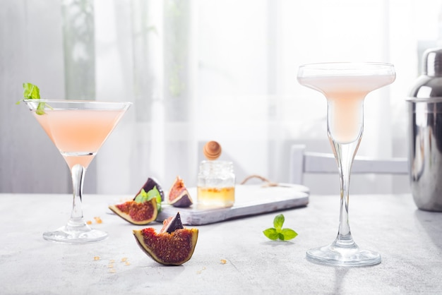 Jack rose cocktail with figs and honey on light background over windows