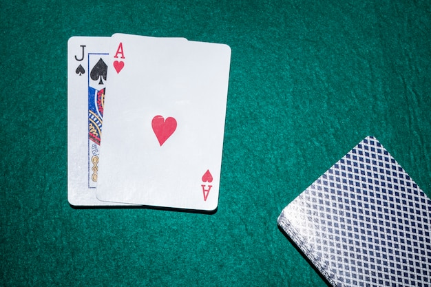 Jack of spade and heart ace playing card on green poker table
