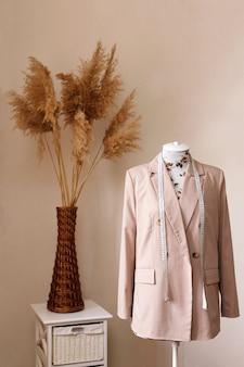 베이지 색 재봉사 배경에 센티미터와 마네킹에 재킷