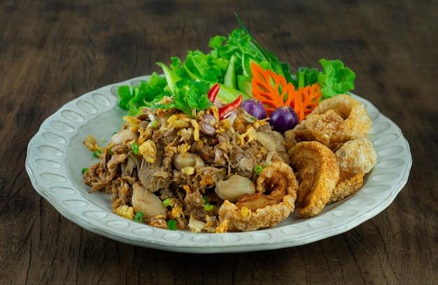 Jackfruit curry paste stir fried with crispy garlic served crispy pork and fresh vegetable  northen local thai food lanna style sideview