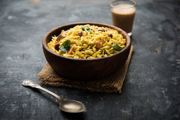 Jada poha namkeen chivda or thick pohe chiwda is a jar snack with a mix of sweet, salty and nuts flavours, served with tea. selective focus