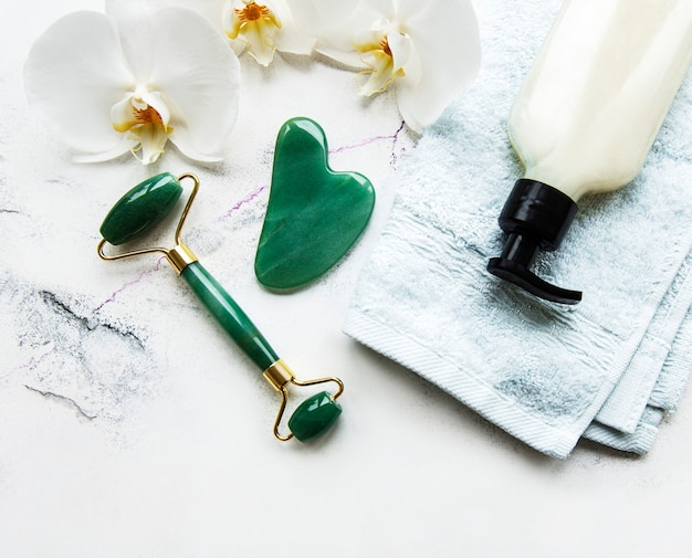 Jade face roller for beauty facial massage therapy. flat lay on wtite marble table