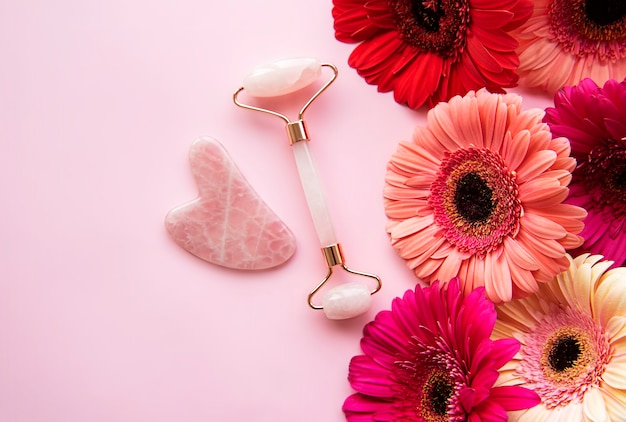 Jade face roller for beauty facial massage therapy and gerbera flowers. flat lay on pink background