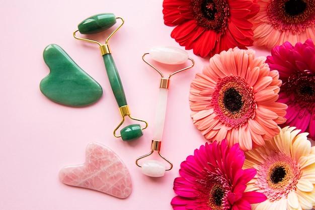 Нефритовый валик для косметического массажа лица и цветы герберы. плоская планировка