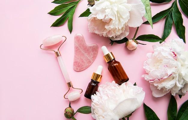 美容フェイシャルマッサージセラピー、マッサージオイル、ピンクの牡丹用の翡翠のフェイスローラー。