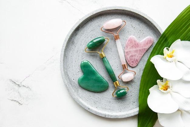 美容フェイシャルマッサージ療法のための翡翠のフェイスローラー。白い大理石のテーブルの上に平らに横たわっていた