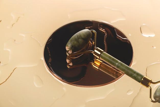 물방울 사이의 둥근 거울에 비취 녹색 얼굴 마사지 롤러 피부 수분 및 마사지 개념