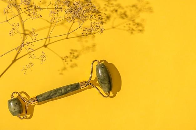 마른 꽃과 함께 옥 녹색 롤러입니다. 노란색 배경에. 페이셜 케어.