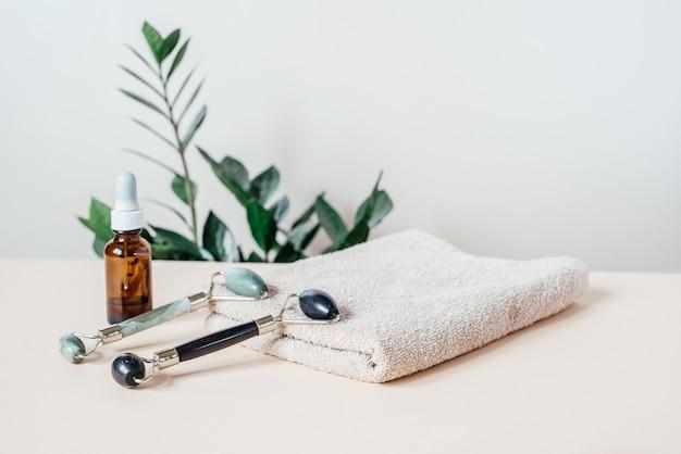 밝은 파스텔 배경의 수건과 세럼 병에 있는 제이드 구아샤 마사지 롤러, spa 휴식, 얼굴 및 피부 관리 개념