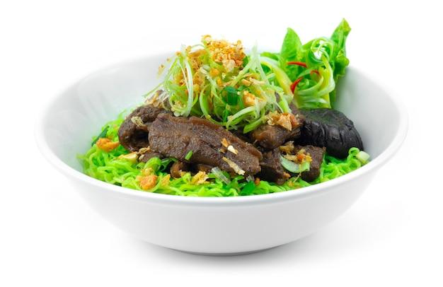 ネギとカリカリにんにくを乗せた牛肉の煮込みと翡翠麺中華料理スタイルの装飾野菜の側面図