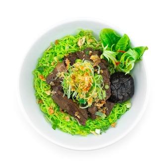 ネギとカリカリにんにくを乗せた牛肉の煮込みと翡翠麺中華料理スタイルの装飾野菜のトップビュー