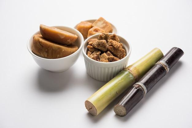 변덕스러운 배경 위에 사탕수수를 곁들인 jaggery 또는 gur. 선택적 초점