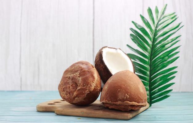 나무 배경에 코코넛과 잎의 절반이 있는 야자 또는 코코넛의 재거리 또는 설탕