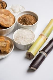 Jaggery, sugar variety 및 sugarcane - 사탕수수 또는 ganna의 부산물은 변덕스러운 배경 위에 배치됩니다. 선택적 초점