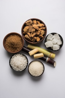 Jaggery, sugar variety and sugarcane - by-products of sugar cane or ganna placed over moody background. selective focus