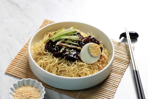 Чаджанг мён или чжаджангмён корейская ноддл с соусом из черной фасоли, подается с огурцом и кунжутом